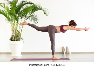 Sportive woman doing Warrior 3 or Virabhadrasana III yoga pose, practicing indoors, standing on one foot on the mat and stretching her body horizontally. Side view in full length
