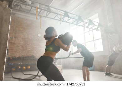 Sportive woman lifting a heavy sandbag while having workout at industrial gym. Group training, teamwork concept. Selective focus