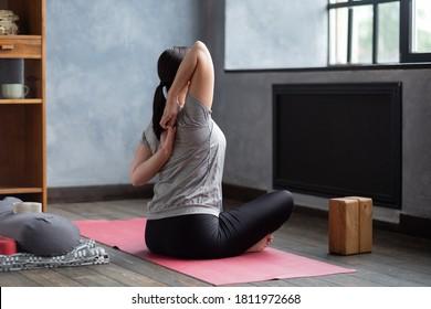 Sportive woman making yoga asana gomukhasana in siddhasana at home. Rear view.