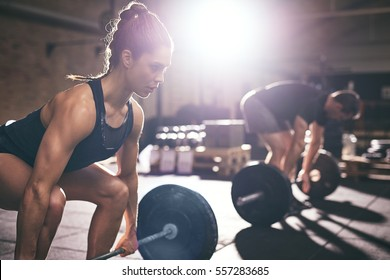 Sportive woman and man lifting a dumbbell from squats in light gym.