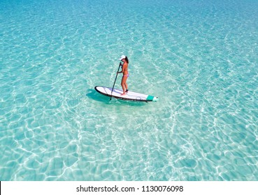 Sportive woman on a stand up paddle board (SUP) over turquoise waters in the Maldives