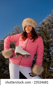 Sportive woman in pink jacket with ice skates