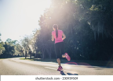 Sportive woman running outside at sunrise on the road. Fitness and wellness concept.