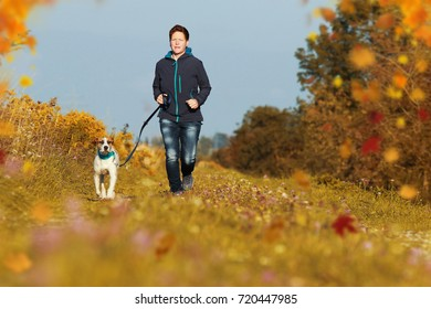 Sportive woman runs with her dog on a leash in autumn exterior shot