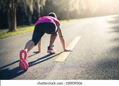 Sportive woman working out outdoors. Young lady doing exercises and ready to start running. Health and sport concept.