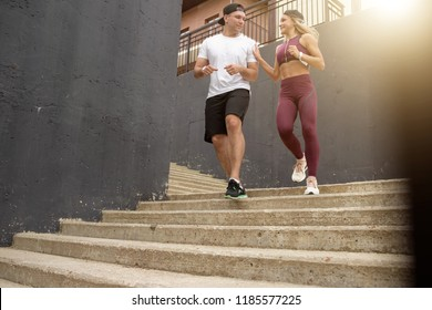 Sportive young couple running on stairs in morning city, jogging in urban area with starecases.