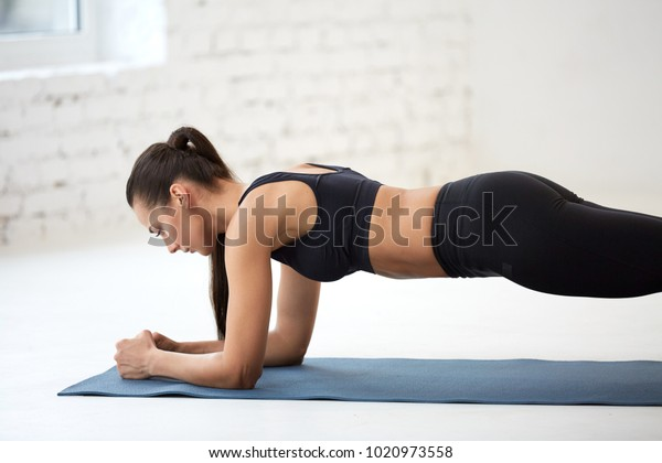 Sportive young girl wearing black top and pants doing physical exercises at white background, warming up, physical activity concept, plank.