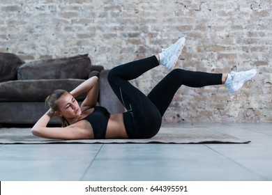 Sportive young lady doing crisscross crunch exercise lying on a rug at modern studio