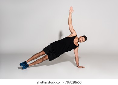 sportive young man doing side plank