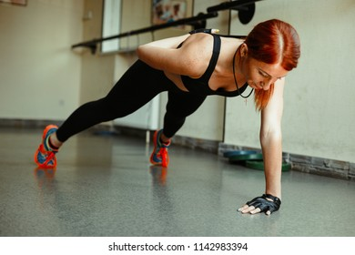 sportive young woman doing push ups in gym