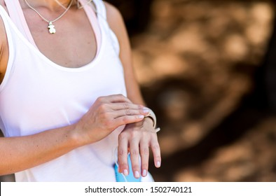 Sportive young woman measure pulse on watch, girl running in park. Hands on brown background with space for text. Sport wear and wearables. White sport clothes.