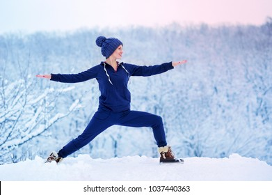 Sportive young woman practicing warrior yoga pose in winter time