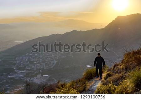 sportman-walking-through-cliff-against-4