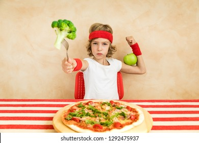 Sportrsman nerd child eating superfood. Geek kid holding broccoli and apple. Healthy eating and lifestyle concept. Green vegetarian food