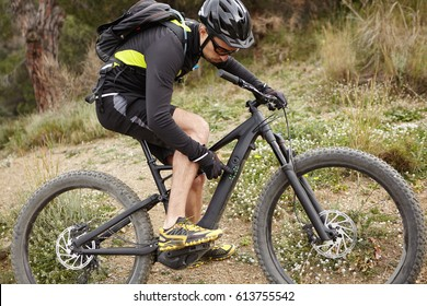 Sports, active lifestyle, fitness, extreme and adrenaline concept. Outdoor shot of handsome biker in protective equipment pressing buttons on control panel on his pedelec, switching speed mode