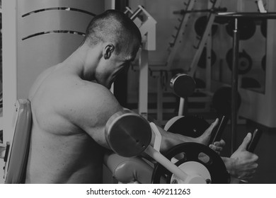 Sports activities in the gym. Strong man doing exercises