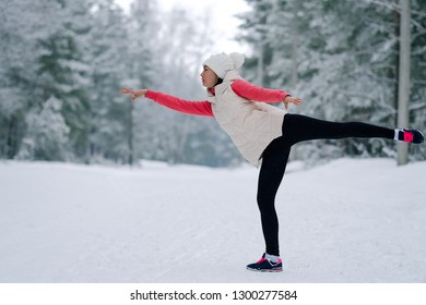 Sports activities on the street in winter. The girl in sportswear runs in the park