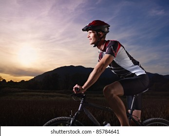 sports activity: young adult cyclist riding mountain bike in the countryside. Horizontal shape, side view, copy space