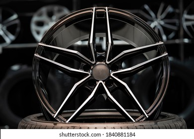 sports alloy wheel rim with carbon cover, in the hall of the car shop on the background of wheels. Front view.