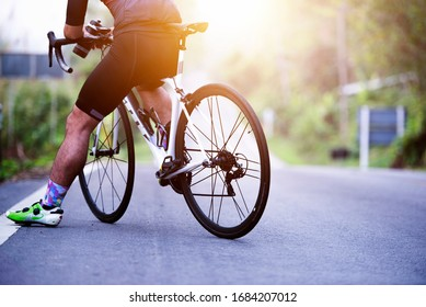 Sports. Asian cyclists ride bicycles on the open road to sunset.