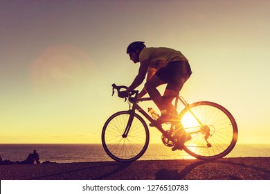 Sports athlete silhouette. Road bike cyclist biking near ocean. Professional triathlete riding bike on an open road to the sunset. Active healthy man sport lifestyle.