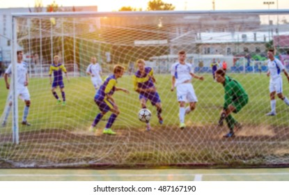 Sports background blur. Bokeh spectacular game of football. Intense attack players in the soft backlight of the setting sun as a backdrop for the sporting poster