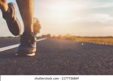 Sports background. legs of Runner feet running on road