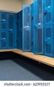 Sports background of a locker room with blue metal cage style lockers, some open, with a wooden bench