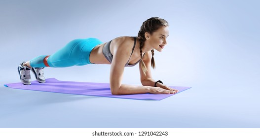 Sports Background/ Muscular woman on a plank position.