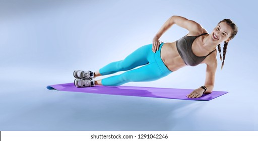 Sports Background. Muscular woman on a plank position. Side plank. Planks variation.