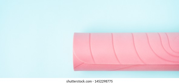 Sports background with pink rolled sports Mat, yoga on blue background with space for text.