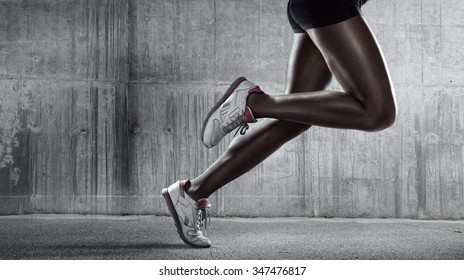 Sports background. Runner. Side view of a jogger legs on concrete wall