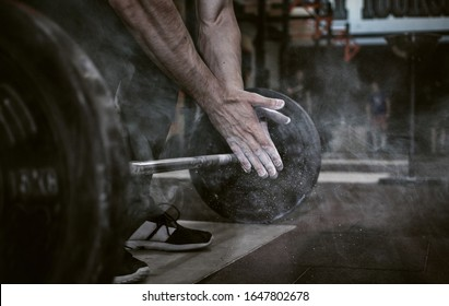 Sports background. Young athlete getting ready for weight lifting training. Powerlifter hand in talc preparing to bench press.