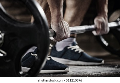 Sports background. Young athlete getting ready for weight lifting training. Powerlifter hand in talc preparing to bench press
