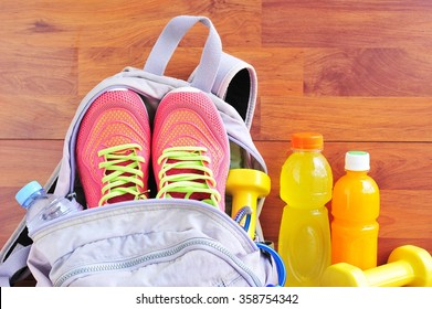Sports bag with equipment on wooden floor.