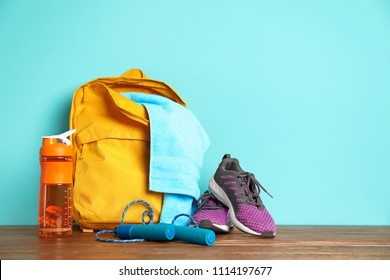 Sports bag and gym equipment on wooden floor against color background