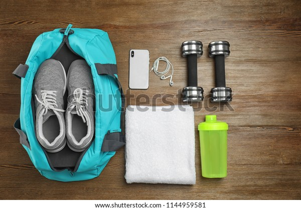 Sports bag and gym equipment on wooden background, top view