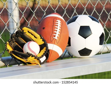 Sports balls. Soccer ball, american football and baseball in yellow glove. Outdoors
