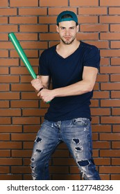 Sports and baseball training concept. Guy in dark blue tshirt holds bright green bat. Man with bristle in green cap on red brick wall background. Player with smiling face plays baseball.
