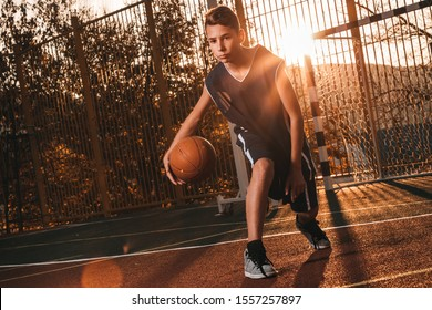 Sports and basketball. A young teenager in a black tracksuit is playing a basketball. Sunset light