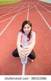Sports beautiful woman on stadium drinking water
