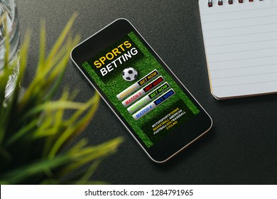 Sports betting website in a mobile phone screen placed over a black desk.