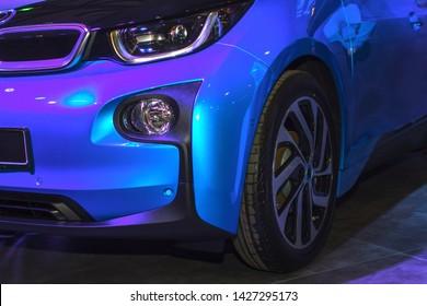 Sports blue car close up. Beautiful headlights and wheels.