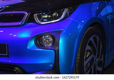 Sports blue car close up. Beautiful headlights and wheels.