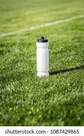 Sports bottle on football field on green grass
