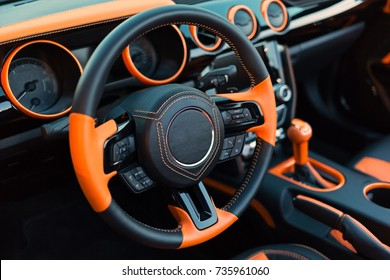 Sports car interior with orange accents.