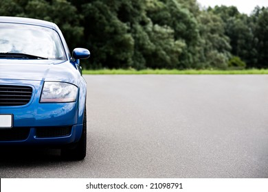 sports car - modern blue coupe on road, focus on headlight with ample copyspace