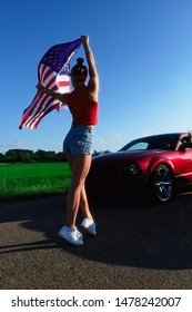Sports cars at the start, speed and excitement. Top gear,Beautiful sexy blonde girl with a sports figure gives the go-ahead to cars with the American flag, attention to the start. Ready, set, go.