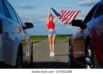 Sports cars at the start, speed and excitement,beautiful sexy blonde girl with a sports figure gives the go-ahead to cars with the American flag, attention to the start. Ready, set, go/