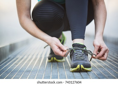 Sports in a city - woman tying her jogging shoe. Shallow DOF, focus on the shoe.